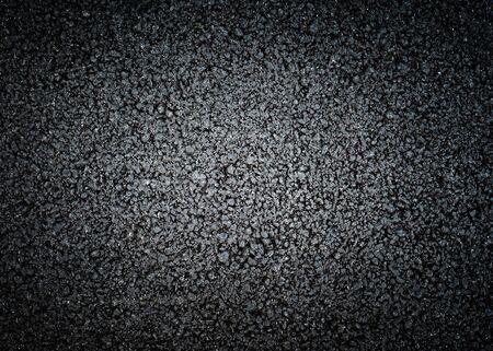 Black asphalt texture, dark background with strong vignette