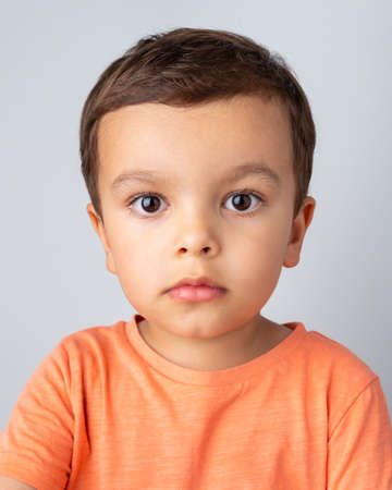 Cute three year old boy portrait, toddler wearing orange tee shirt and shot against a light grey background.
