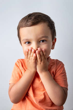 Cute three year old boy portrait, toddler covering his mouth with both hands. Banque d'images