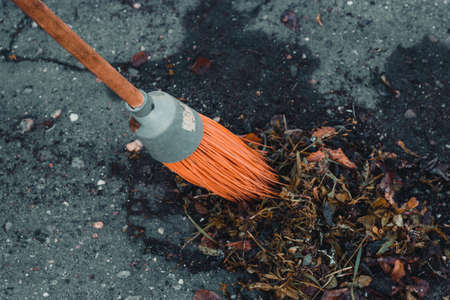 Orange broom sweep up debris and foliage
