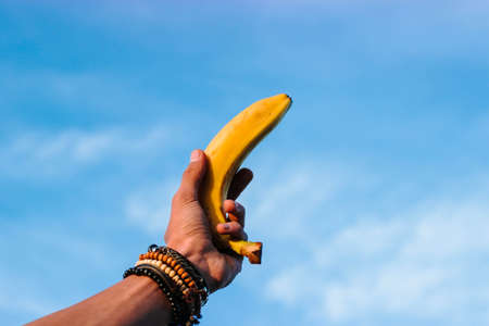 Yellow banana hold in hand with bracelets against the blue sky