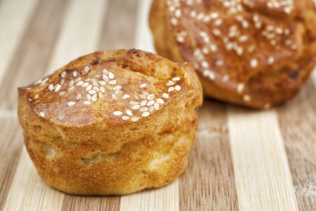 Two cornbread muffins with sesame photographed on wooden table. Studio shot.