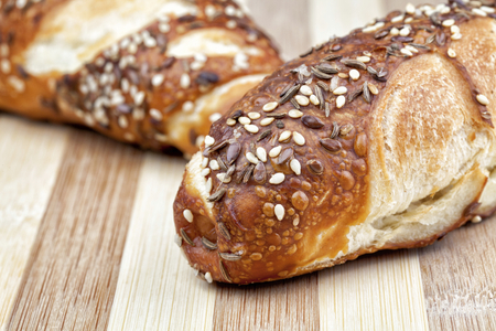 Kind of Bavarian bread with cumin, sesame and linseed photographed on wooden table. Studio shot.