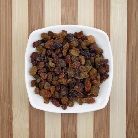 Raisins served in white plate on a wooden table. Photo taken from above.