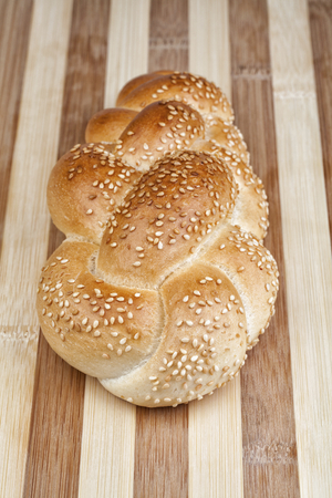Crispy and perfectly baked sesame bread made of wheat flour. Studio shot on wooden table.