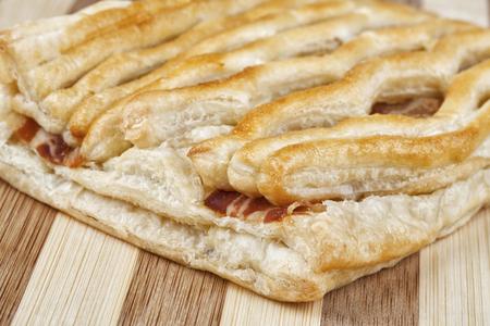 Close up shot of danish pastry with crispy grilled bacon. Studio shot on wooden table. Reklamní fotografie