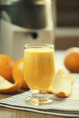 Glass of real freshly squeezed orange juice. Ambient light with juicer and oranges in background.