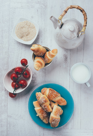 Beautifull home made croiisants photographed from above on rustic wooden table. Table top food photography.