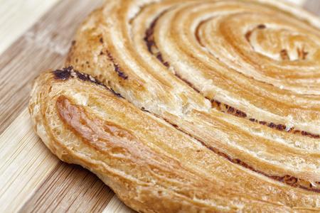 Closeup shot of danish pastry swirl with milled hops. Studio shot on wooden table. Reklamní fotografie
