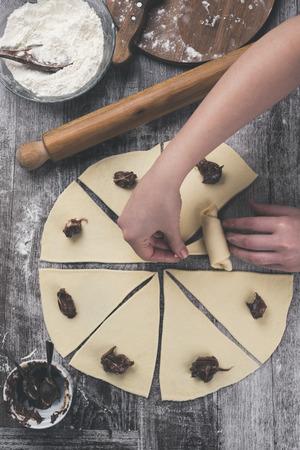 Woman's hands making delicious croissants