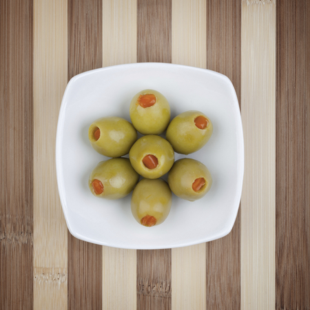 Green olives in white plate on wooden table. Studio shot. Selective focus