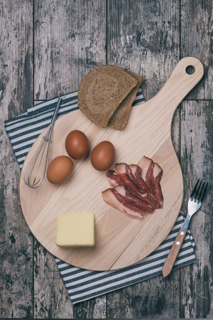 Vintage photo of kitchen cutting board with meal ingredients photographed from above on old rustic wooden table. Reklamní fotografie