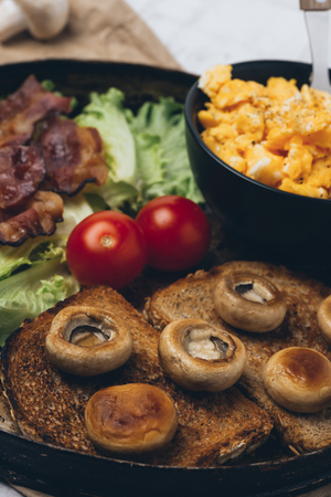 Close shot of tasty and fresh traditional meal with toast, scrambled eggs, fried bacon, mushrooms, green salad and cherry tomatoes. Reklamní fotografie