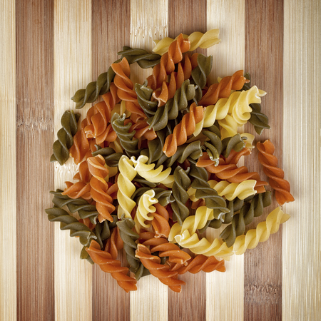 Heap of raw and colorful fusilli corkscrew pasta photographed from above on wooden table. Studio shot.