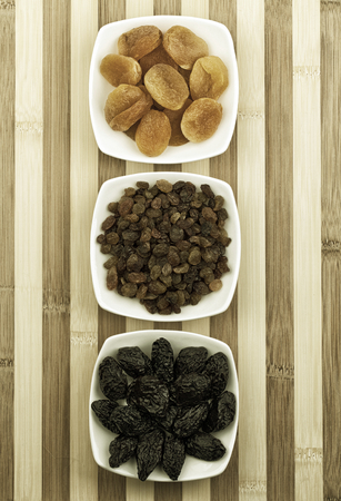 Dried fruits in white bowls on wooden table photographed from above. Photo is sepia toned and little noise was added.