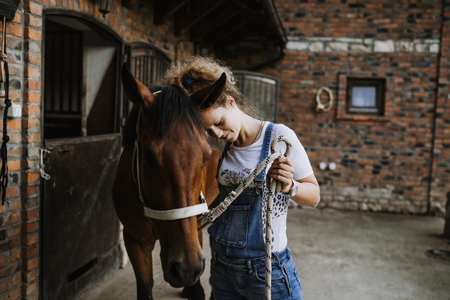 Young woman taking care of her horse. Reklamní fotografie