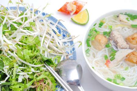 Bun cha ca of Vietnamese rijstvermicelli met gegrilde vis en kruiden op een witte achtergrond