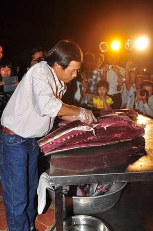 TUY HOA, VIETNAM - APRIL 1, 2014: An expert is performing tuna fillet techniques at Vietnam seafood festival in Tuy Hoa city