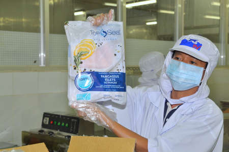 antidumping: TIEN GIANG, VIETNAM - MARCH 2, 2013: A Worker is showing a certified pangasius fish product in a seafood processing plant in Tien Giang, a province in the Mekong delta of Vietnam Editorial