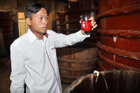 Phu Quoc, 베트남 - 우리 모두의 2013 년 8 월 19 일 : 전문가는 Phu Quoc 섬의 발효 탱크에서 베트남에서 전통적인 소스는 생선 소스 샘플의 품질을 검사합니다