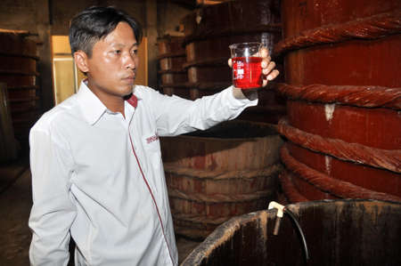 PHU QUOC, VIETNAM - AUGUST 19, 2013: An expert is checking the quality of the fish sauce sample which is a traditional sauce in Vietnam, from a fermented tank in Phu Quoc island.