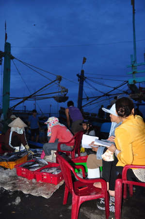 NHA TRANG, VIETNAM - FEBRUARY 21, 2013: Women workers are collecting and sorting fisheries into baskets after a long day fishing in the Hon Ro seaport, Nha Trang city