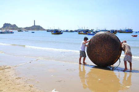 forage fish: LAGI, VIETNAM - FEBRUARY 26, 2012: Local fishermen are preparing their basket boat for a new working day in the Lagi beach Editorial