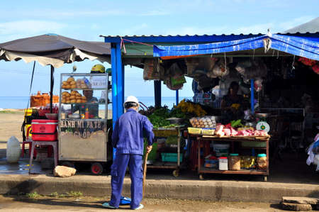 con dao: CON DAO, VIETNAM - JULY 2, 2012: A man is sweeping in front of his food street vendor on the Con Dao island of Vietnam