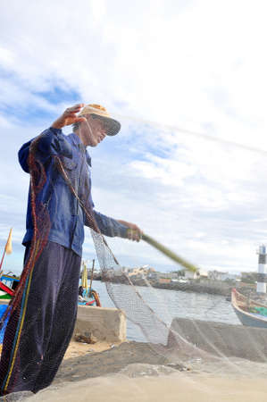 forage fish: QUANG NGAI, VIETNAM - JULY 31, 2012: A fisherman is removing anchovies fish from his fishing net to begin a new working day in Ly Son island Editorial
