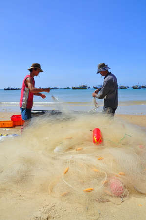 LAGI, VIETNAM - FEBRUARY 26, 2012: Local fishermen are preparing their fishing nets for a new working day in the Lagi beach Redakční