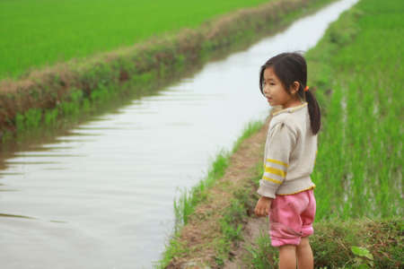 NAM DINH, VIETNAM - MARCH 28, 2010: A little girl is in the paddy field in the countryside of the North of Vietnam