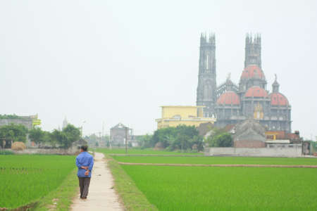 god walking: NAM DINH, VIETNAM - MARCH 28, 2010: A farmer is walking toward a catholic church in a countryside in the North of Vietnam