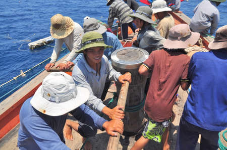 shrimp boat: NHA TRANG, VIETNAM - MAY 5, 2012: Fishermen are trawling for tuna fish in the sea of Nha Trang bay in Vietnam