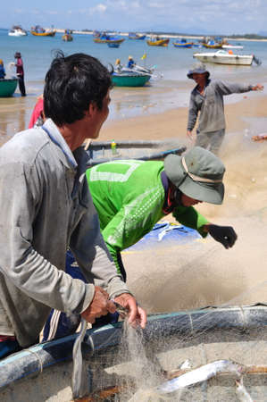 fishing nets: LAGI, VIETNAM - FEBRUARY 26, 2012: Local fishermen are removing fishes from their fishing nets in the Lagi beach
