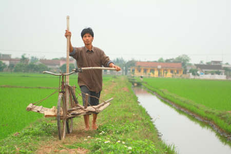 NAM DINH, VIETNAM - MARCH 28, 2010: A farmer in the north of vietnam is going to work on his paddy field Editorial