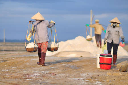 road shoulder: NINH HOA, VIETNAM - MARCH 2, 2012: Vietnamese women are burdening hard to collect salt from the extract fields to the storage fields