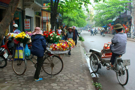 COSTUMERS: NAM DINH, VIETNAM - MARCH 30, 2010: A Florist and a cyclist are waiting for their costumers on a pavement