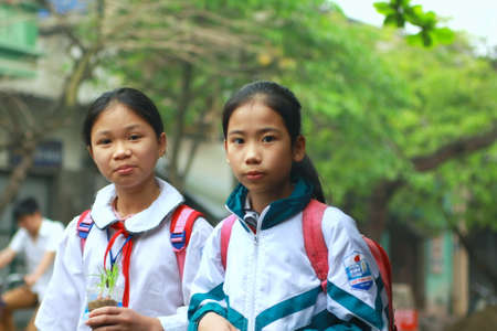NAM DINH, VIETNAM - MARCH 30, 2010: Two pupils are walking to school on the street of Nam Dinh city in the north of vietnam