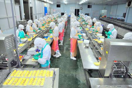 HO CHI MINH CITY, VIETNAM - 3 oktober 2011: De arbeiders werken hard aan een productielijn in een schaal-en schelpdieren fabriek in Ho Chi Minh-stad, Vietnam