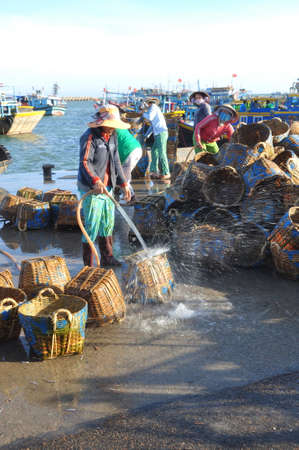 developing country: LAGI, VIETNAM - FEBRUARY 26, 2012: Local women are cleaning their baskets which were used for transporting fishes from the boat to the truck Editorial