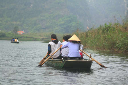 museum visit: NINH BINH, VIETNAM - MARCH 29, 2010: Ferrymen are taking tourists to visit the Trang An Eco-Tourism Complex, a complex beauty - landscapes called as an outdoor geological museum Editorial