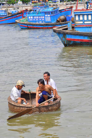 livelihood: NHA TRANG, VIETNAM - OCTOBER 5, 2011: Fishermen are swimming from their vessels to the seaport in a basket boat Editorial