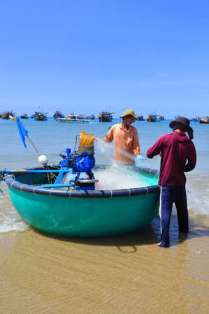 forage fish: LAGI, VIETNAM - FEBRUARY 26, 2012: Local fishermen are preparing their fishing nets for a new working day in the Lagi beach Editorial