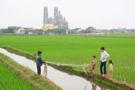 NAM DINH, VIETNAM - MARCH 28, 2010: Children are playing in the paddy field in the countryside of the North of Vietnam