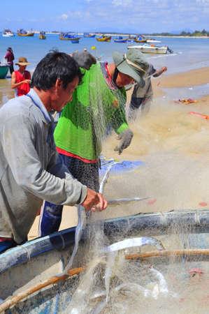 redes de pesca: LAGI, VIETNAM - 26 de febrero de 2012: Los pescadores locales son la eliminación de los peces de sus redes de pesca en la playa Lagi
