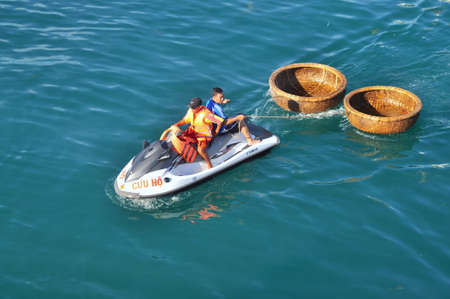 Nha Trang, Vietnam - July 14, 2015: A rescue canoe is towing two basket boat in the sea