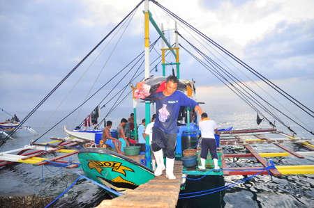 pescador: General Santos, Filipinas - 5 de septiembre de 2015: Pescador están aterrizando atún de barco de pesca en el puerto