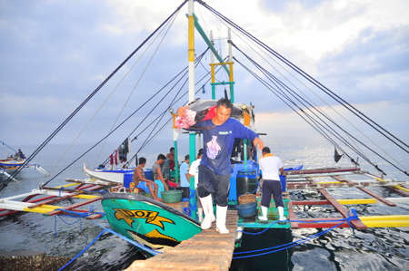 fisherman: General Santos, Philippines - September 5, 2015: Fisherman are landing tuna from fishing boat at the seaport