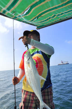 男はベトナムでのエンターテイメントのためのフックで釣りクイーンフィッシュ ブンタウ, ベトナム - 2015 年 10 月 11 日です。