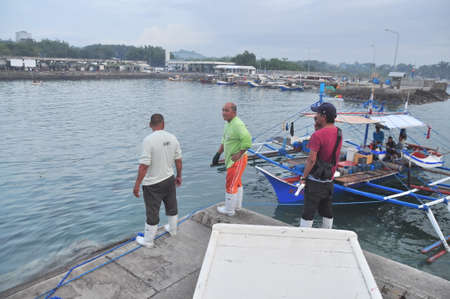 thunnus: General Santos, Philippines - September 5, 2015: Porters are loading tuna from their boats at the seaport Editorial